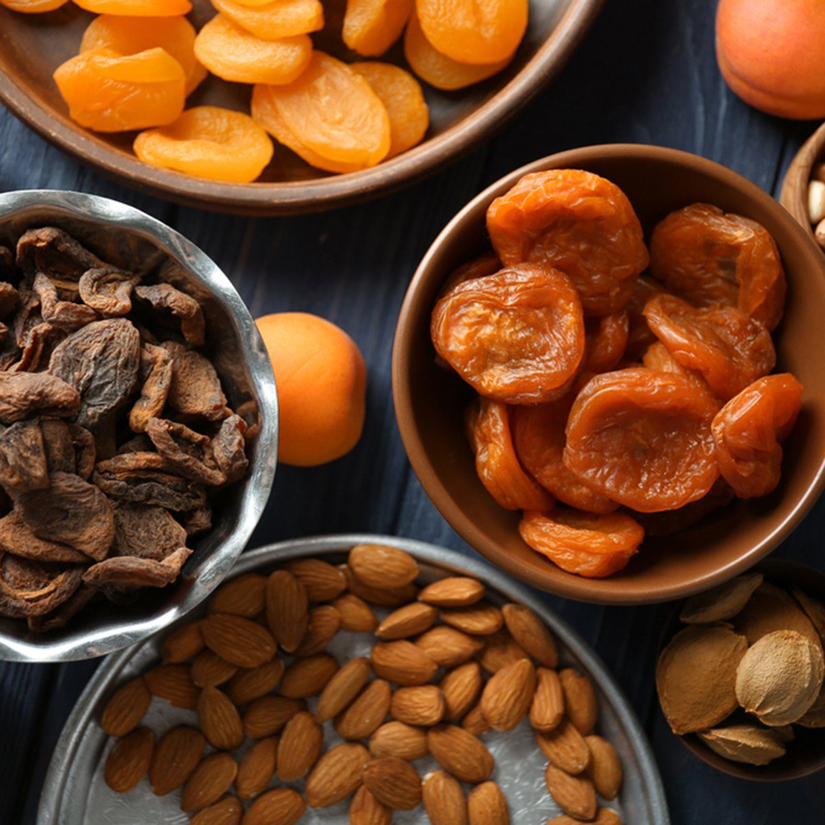 Dried apricots and nuts in different dishes on wooden table; Shutterstock ID 720334081; Job (TFH, TOH, RD, BNB, CWM, CM): TOH