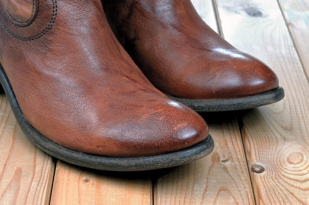 Pair of new classic leather brown cowboy boots on wooden boards. Macro shooting