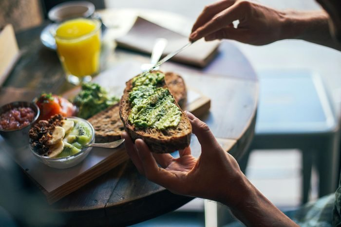 Soft focus shot of man having delicious huge breakfast at cool restaurant or cafe, puts guacamole or avocado spread on top of rye bread toast, ready to indulge and fullfill hunger