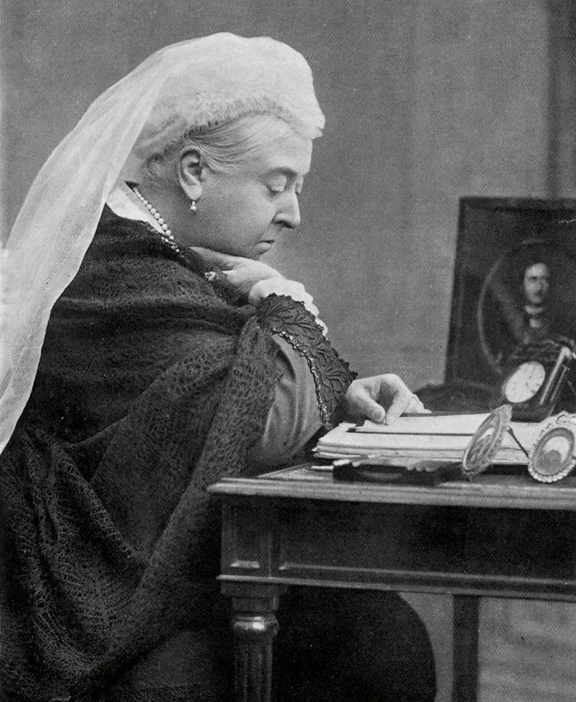 Historical Collection 11 Queen Victoria(1819-1901) Seated at Her Desk in the 1890s with A Picture of Her Deceased Husband Prince Albert by Her Side c. 1890s.