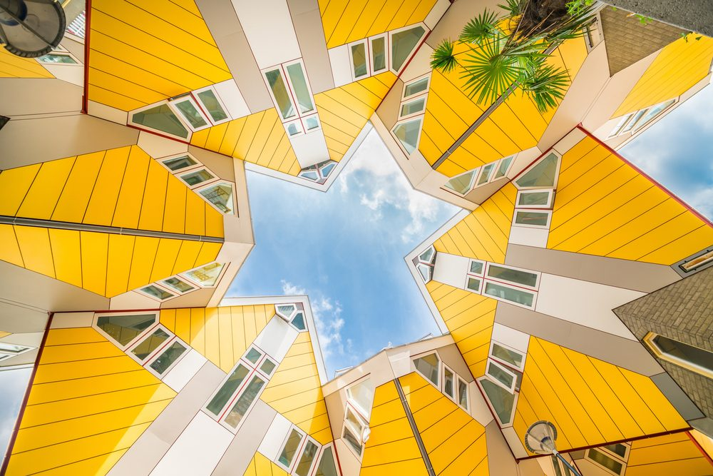 Star shapes formed where six Cube houses tilt into one another and intersect in Rotterdam, a quirky bright yellow architecturally unusual angular cube shape apartment block