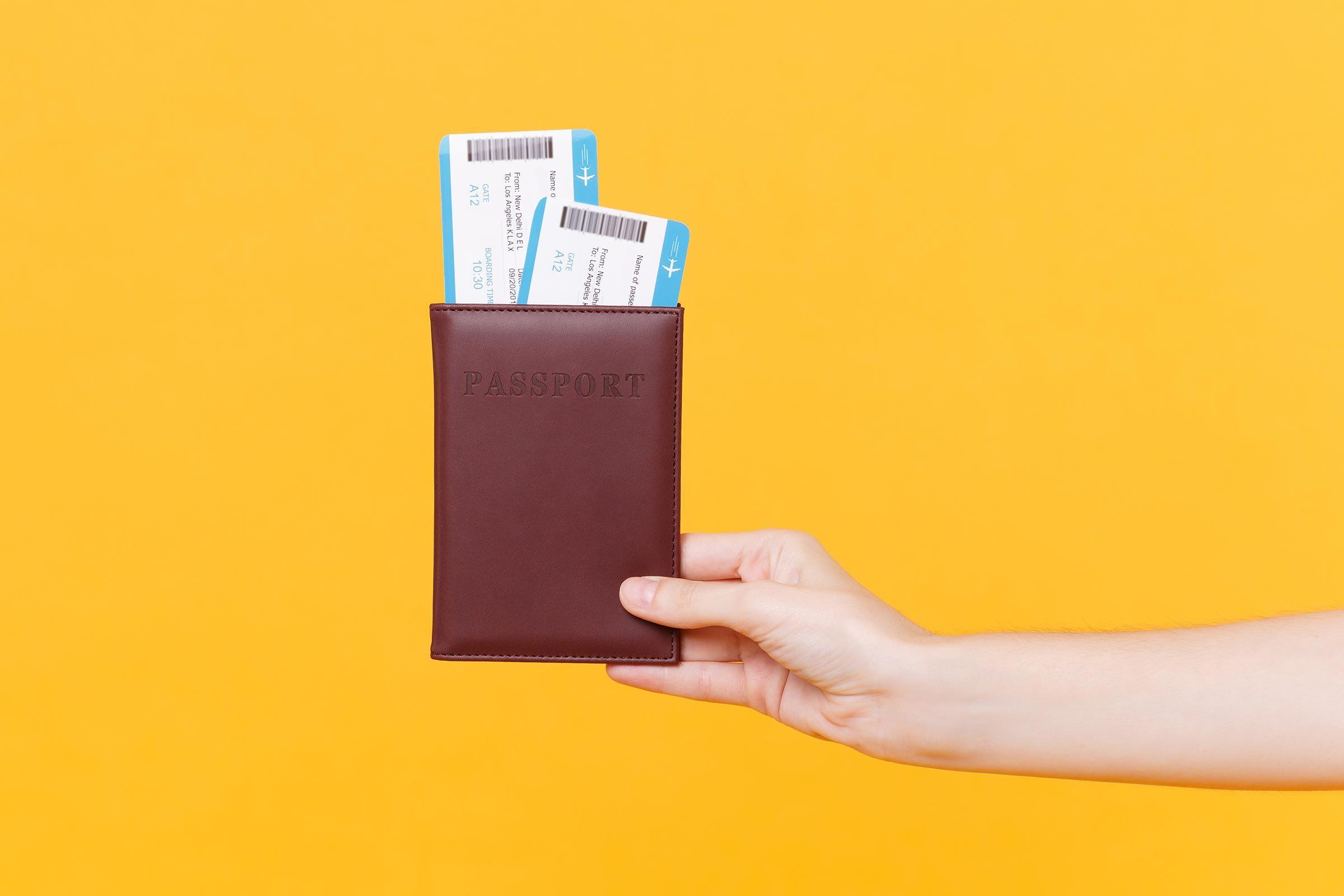 hand holding passport flight tickets boarding pass yellow background