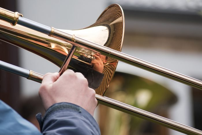trombone player from a brass orchestra with reflection in the music instrument