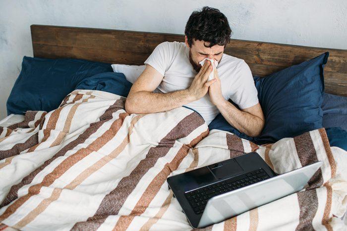 man sick bed laptop