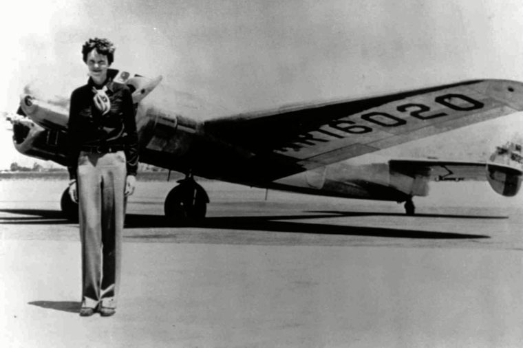 Amelia Earhart, 40, stands next to a Lockheed Electra 10E