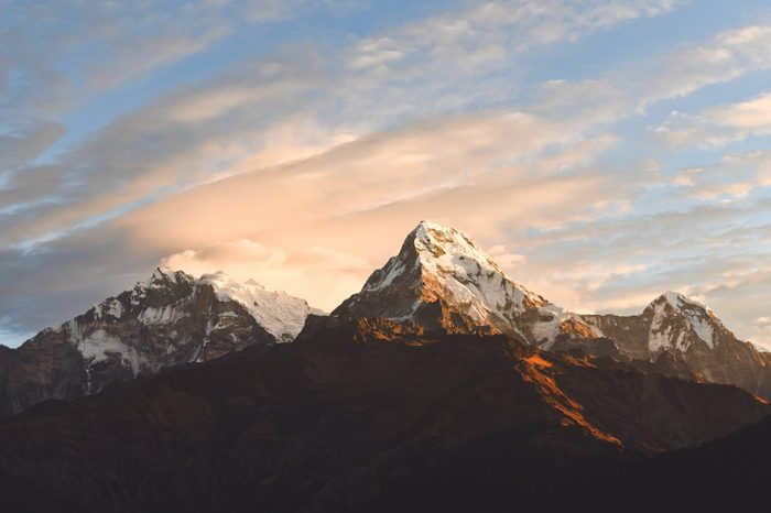 Warm pink and orange sunrise light over Annapurna mountain range with beautiful clouds, view from Poon hill in Himalayas, Nepal