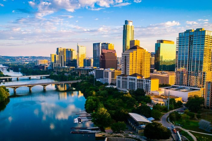 Panoramic sunrise aerial drone view over Lady Bird Lake in Austin Texas the capital city glowing under Morning golden hour sunrise