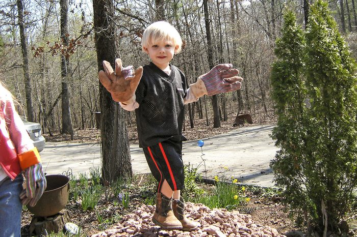 grandson playing in dirt with gardening gloves