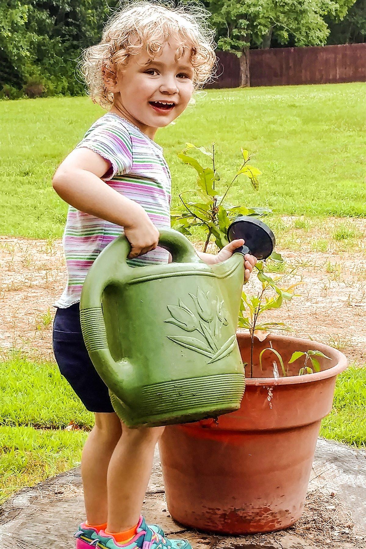 grandaughter watering flower pot