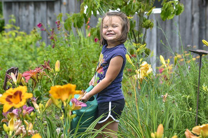 niece watering flowers garden