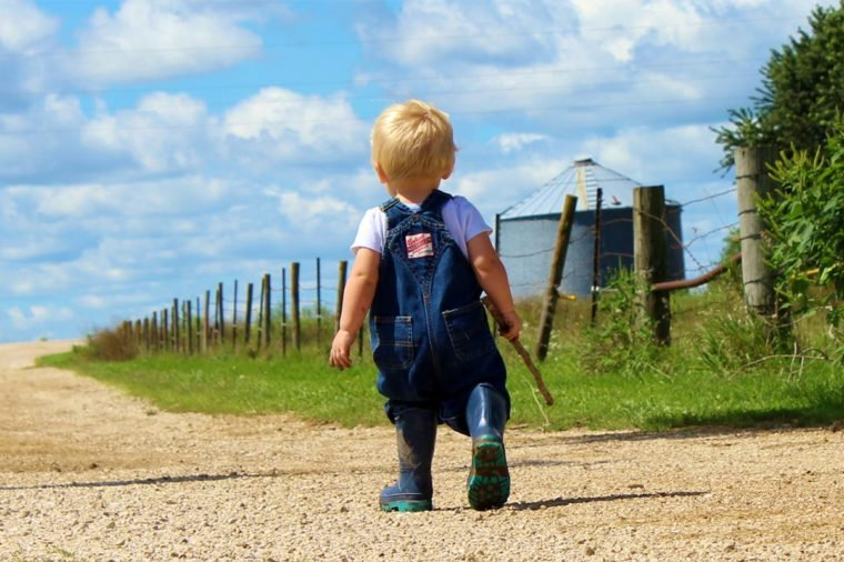 little boy in overalls on dirt road