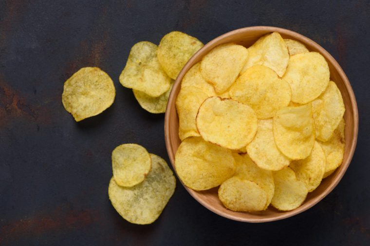 Crispy potato chips in bowl on dark table