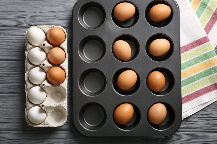 Muffin tin and holder with hard boiled eggs on wooden table