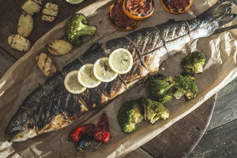 Roasted salmon and vegetables on vintage wooden table