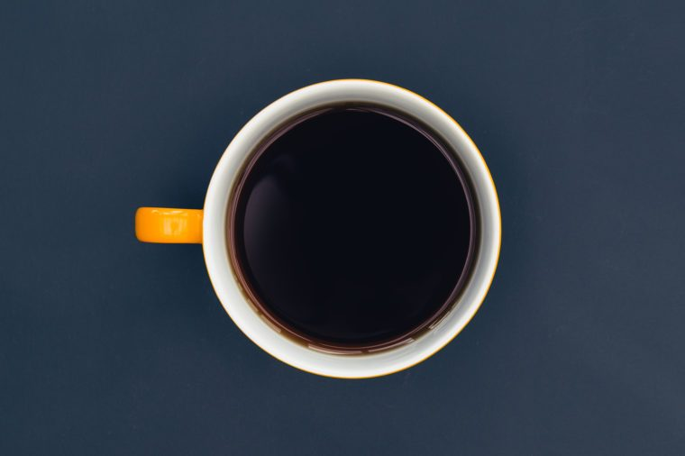 Yellow coffee cup on dark minimal background