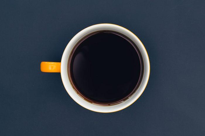 Yellow coffee cup on dark minimal background
