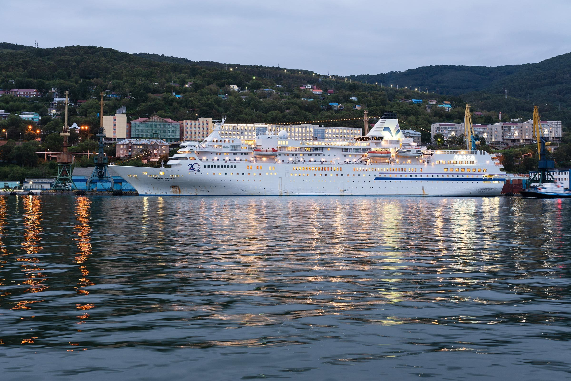 AVACHA BAY, KAMCHATKA PENINSULA, RUSSIAN FAR EAST - 4 SEPTEMBER, 2018: Picturesque night view of white Japanese cruise liner Pacific Venus anchored at pier in Petropavlovsk-Kamchatsky Seaport.