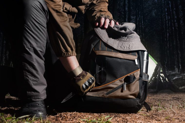 Man in tactical outfit holding a knife and kneeling for backpack with camping and tactical gear on night forest background.