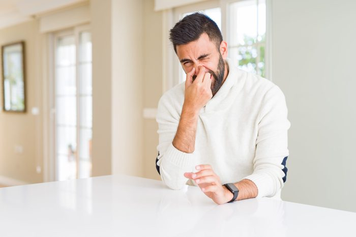 Handsome hispanic man wearing casual white sweater at home smelling something stinky and disgusting, intolerable smell, holding breath with fingers on nose. Bad smells concept.