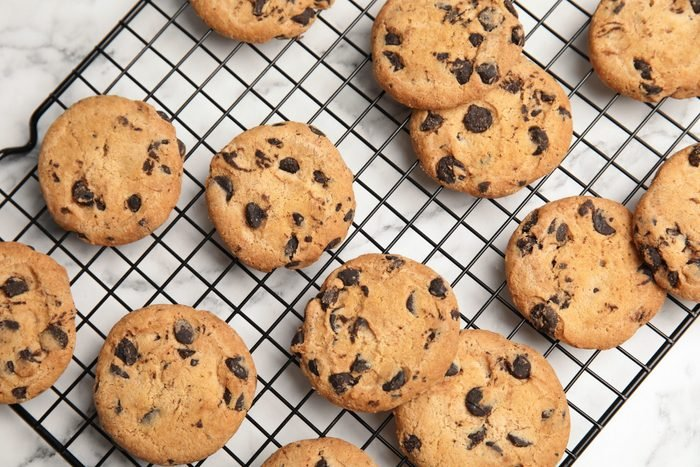 Cooling rack with chocolate chip cookies on marble background, top view