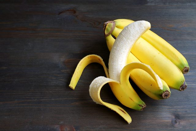 One peeled banana on a bunch of bananas isolated on dark brown wooden table with copy space