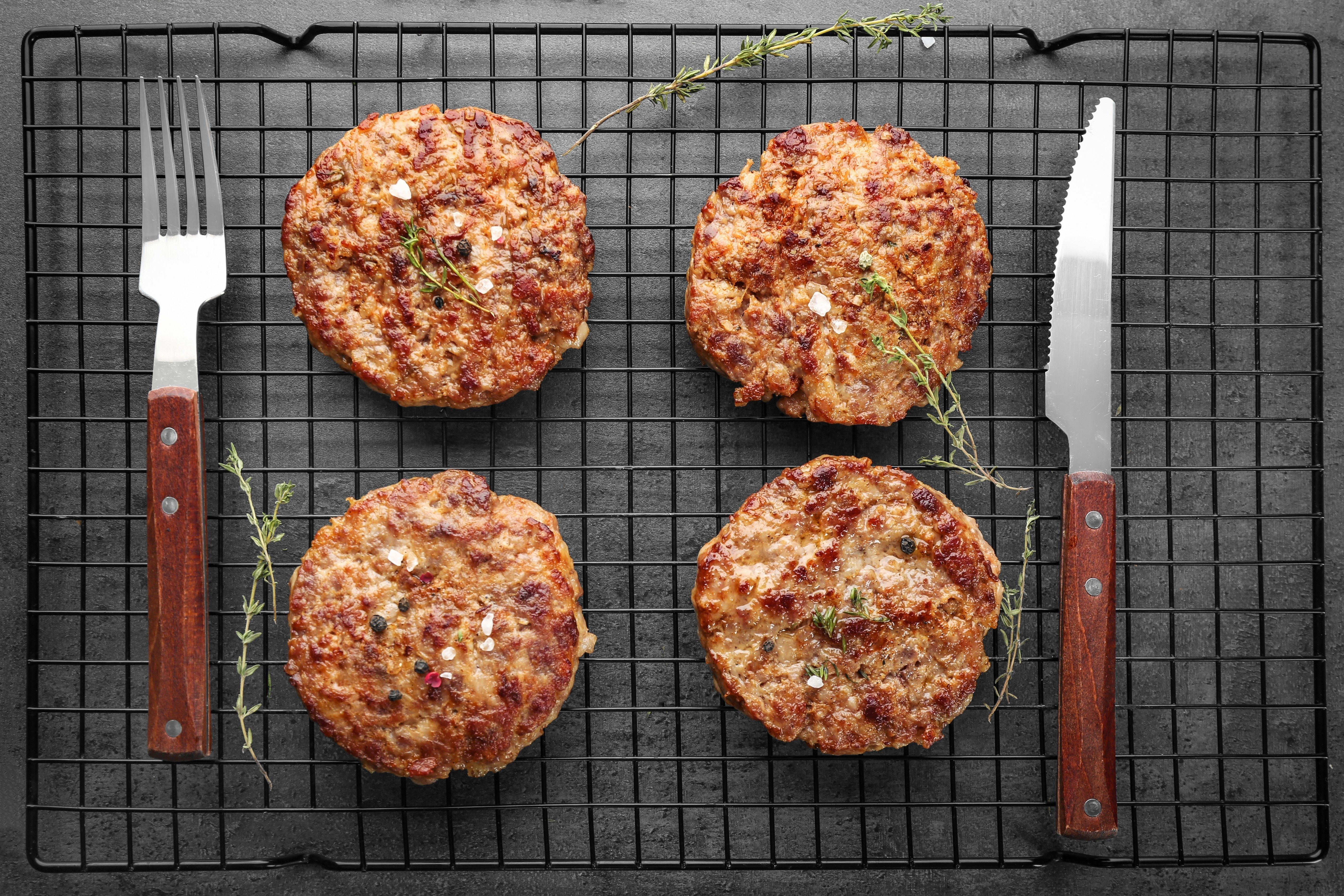 Delicious burger patties on cooling rack