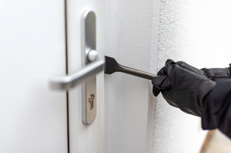 Burglar tries to open a front door with crowbars