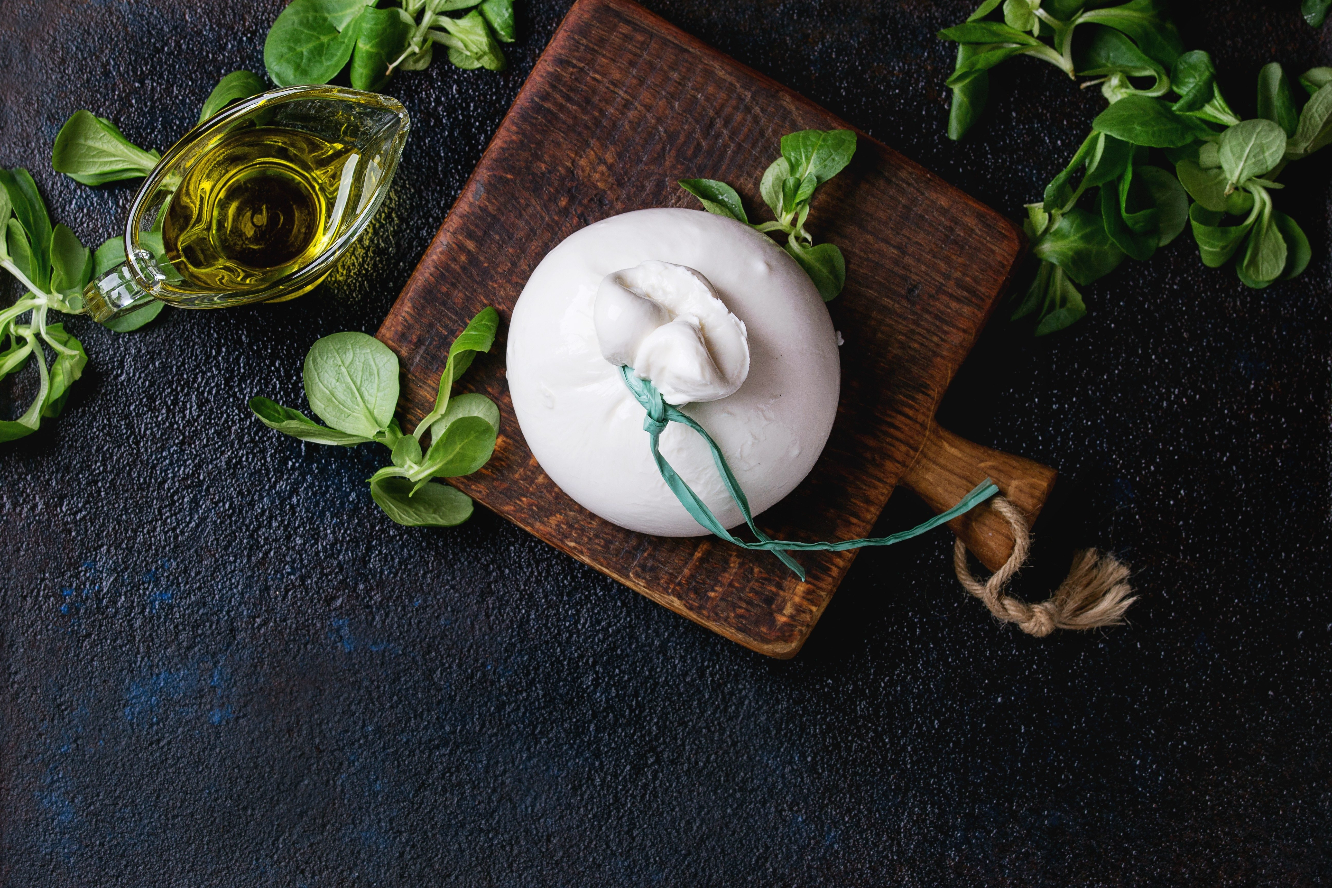 Whole tied Italian cheese burrata on small wooden cutting board served with fresh corn salad and olive oil over dark textural background. Overhead view