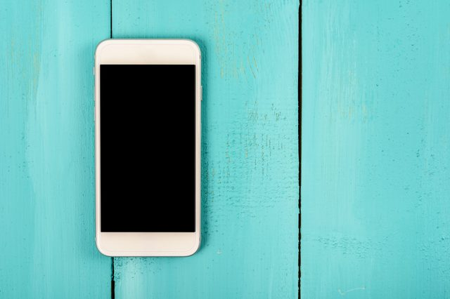 White Mobile Phone With Blank Screen On Wood Table