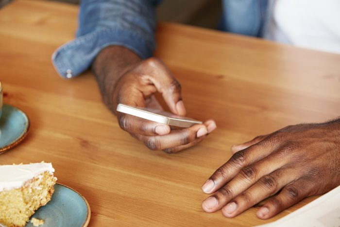 Film effect. Close up shot of African man's hands holding mobile phone while using wireless high-speed Internet connection. Black student texting friends via social networks sitting at a coffee shop