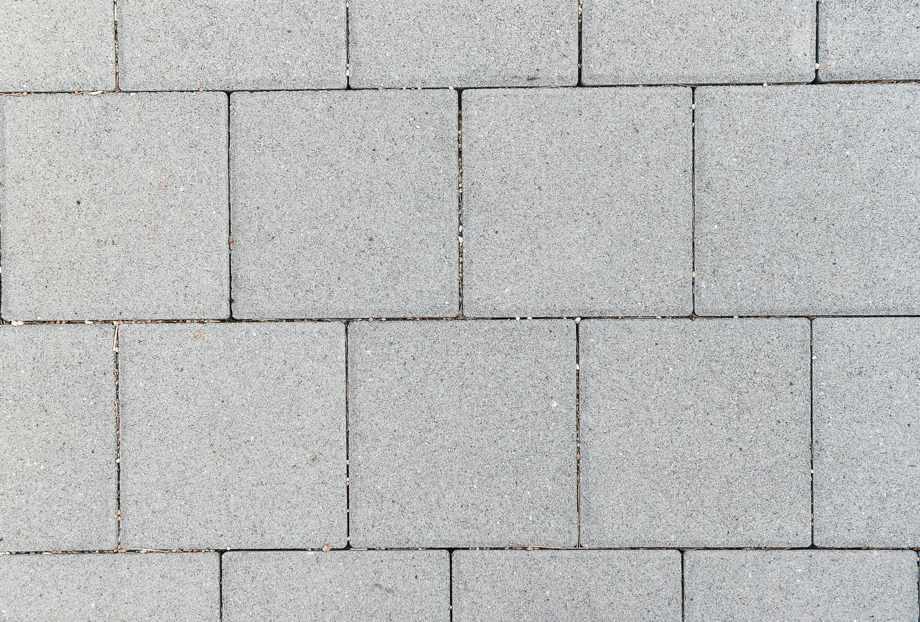 Concrete or cobble gray square pavement slabs or stones for floor, wall or path. Traditional fence, court, backyard or road paving.