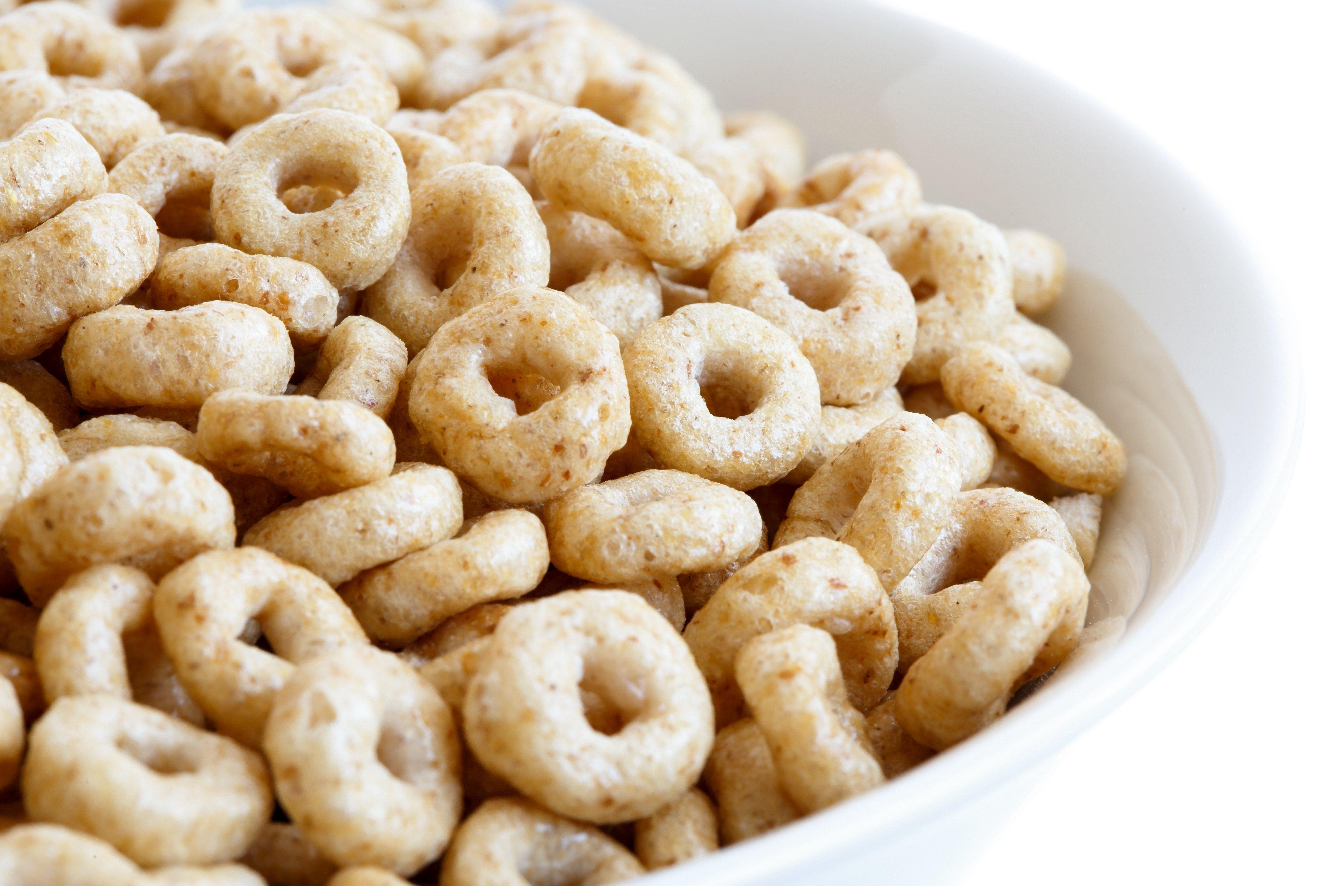 Detail of bowl of honey cheerios on white.