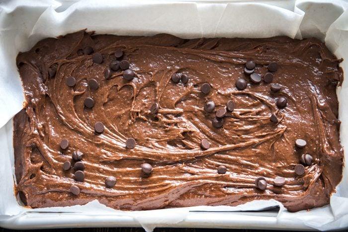 Basic homemade brownie or chocolate cake raw dough in baking pan. Cooking (baking) homemade chocolate cake or brownie.