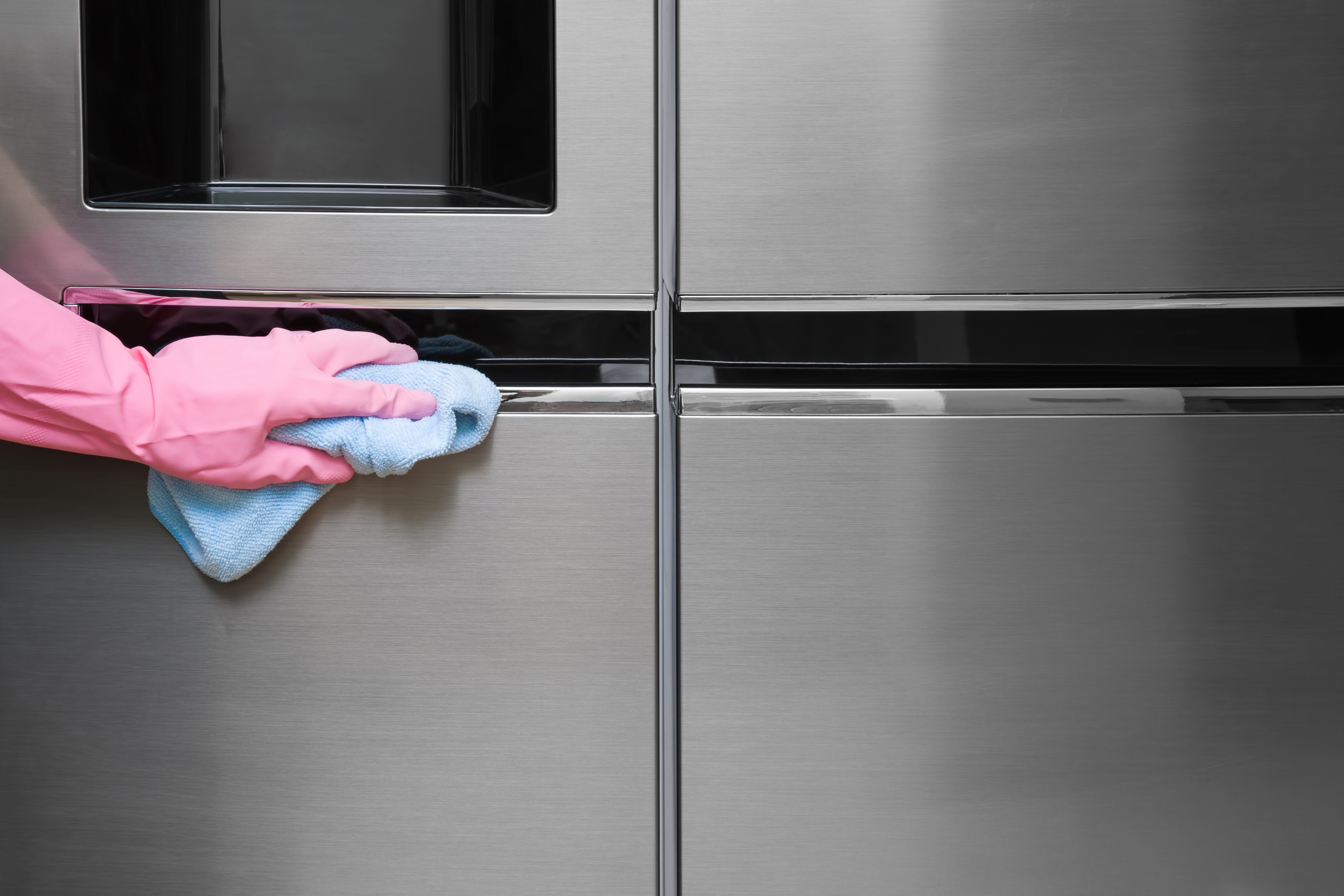 Employee hand in rubber protective glove with micro fiber cloth wiping a fridge's stainless doors. Early spring or regular cleanup. Commercial cleaning company concept.