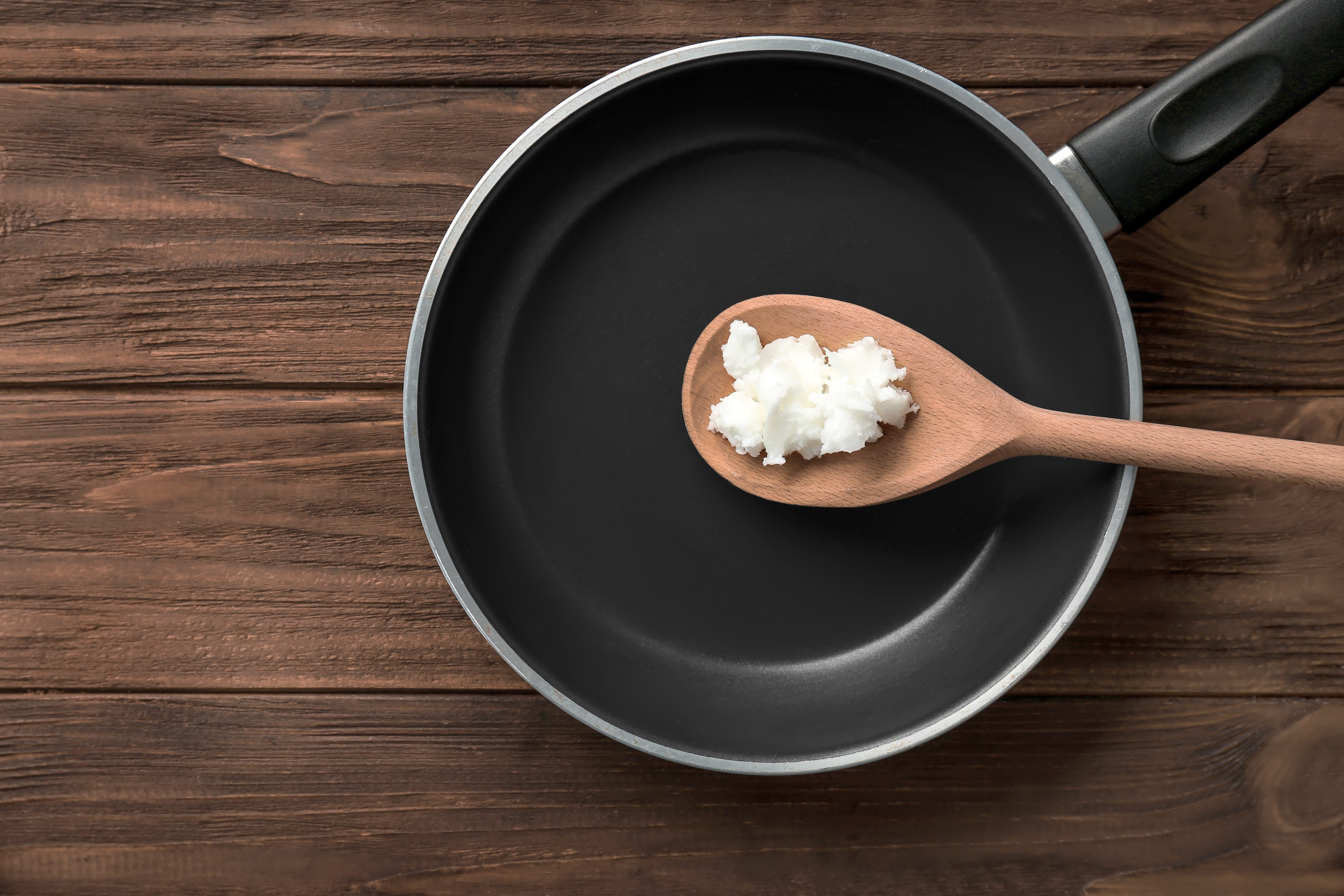 Wooden spoon with coconut oil in frying pan on table