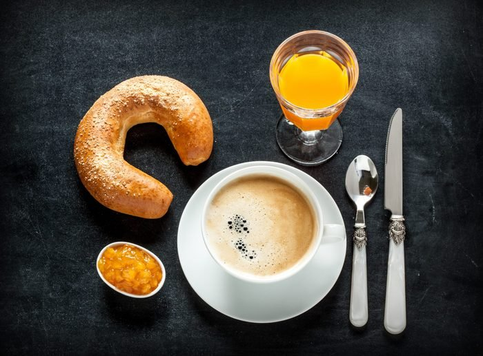 Continental breakfast on black chalkboard background - bar menu. Coffee, orange juice, crescent roll and jam from above.