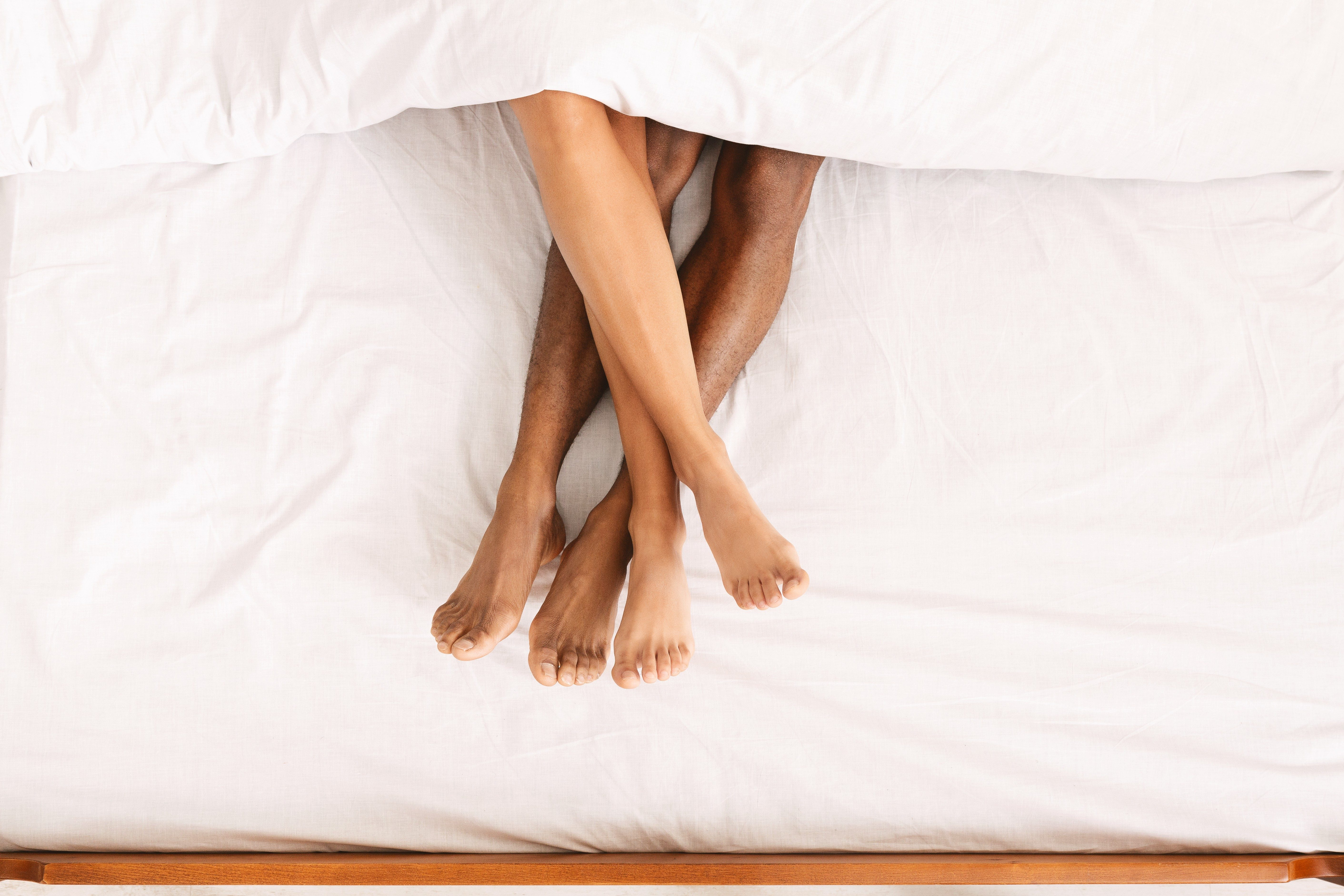 Family connection. Black male and female legs touching together, lying under duvet on bed, top view