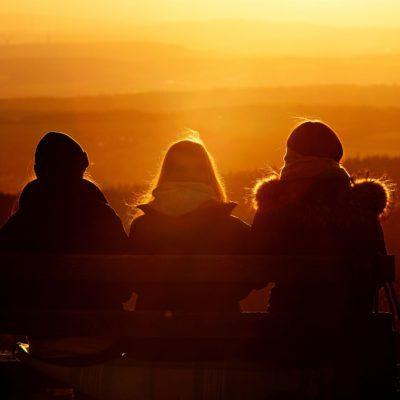 Three women sit and watch the sun set