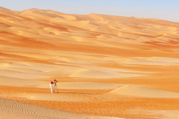 A woman photographing sand dunes in the Rub al Khali or Empty Quarter. Straddling Oman, Saudi Arabia, the UAE and Yemen, this is the largest sand desert in the world.