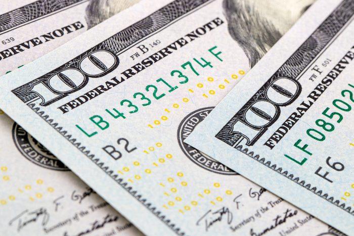 close-up 100 US dollar bills background toned