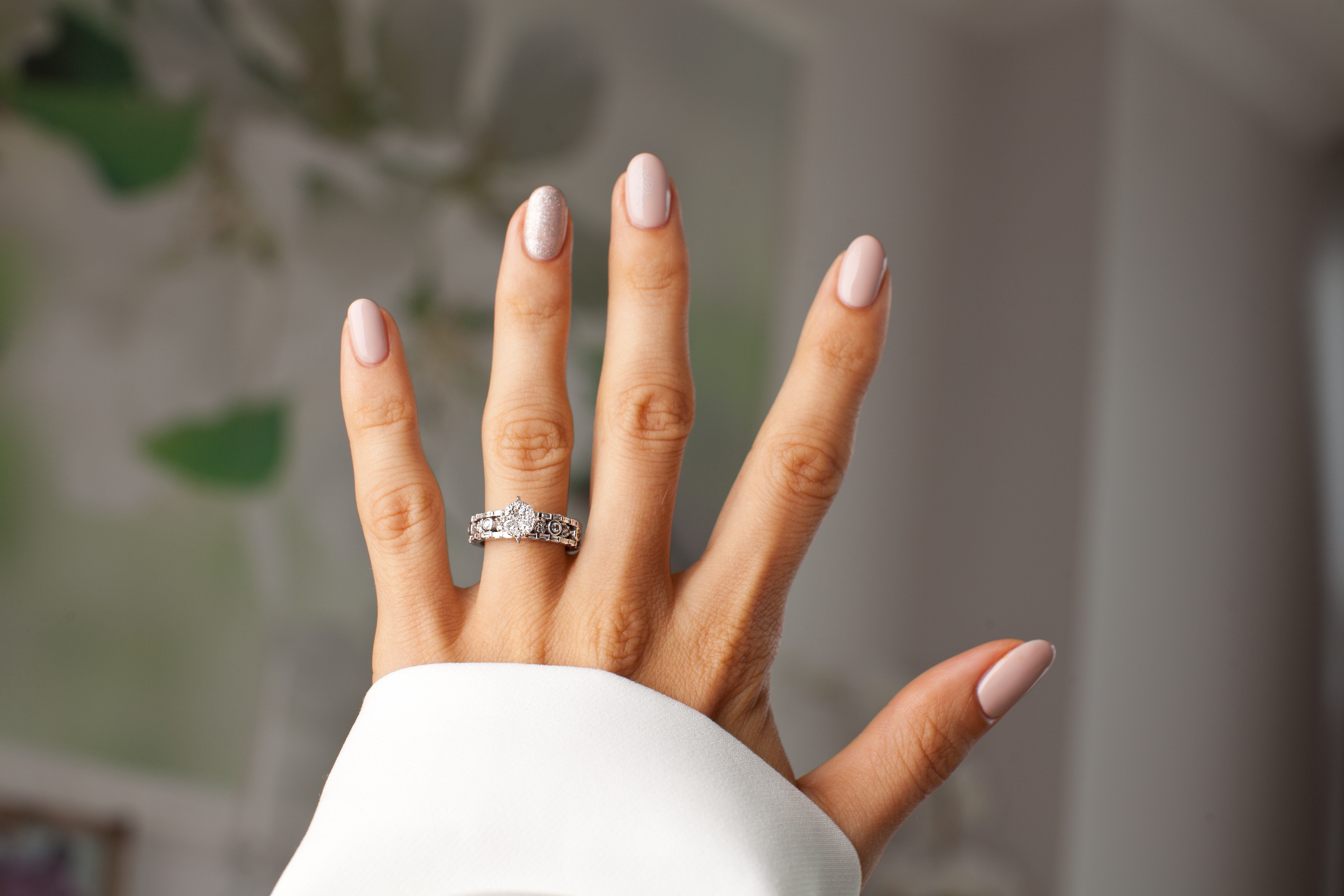 Diamond ring on a finger. Holidays and celebrations concept.