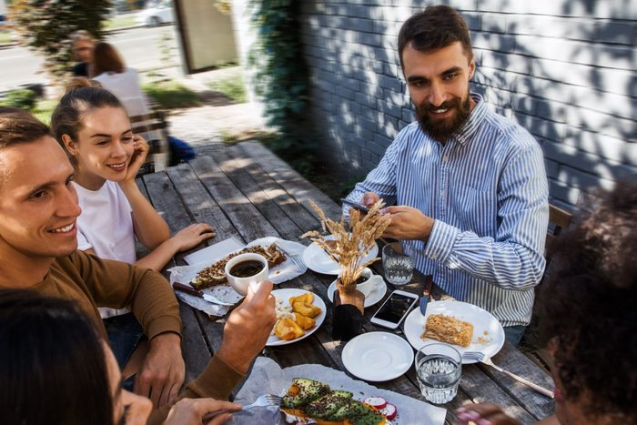Group of friends at restaurant outdoors. People having dinner in a home garden, having fun and enjoing summer