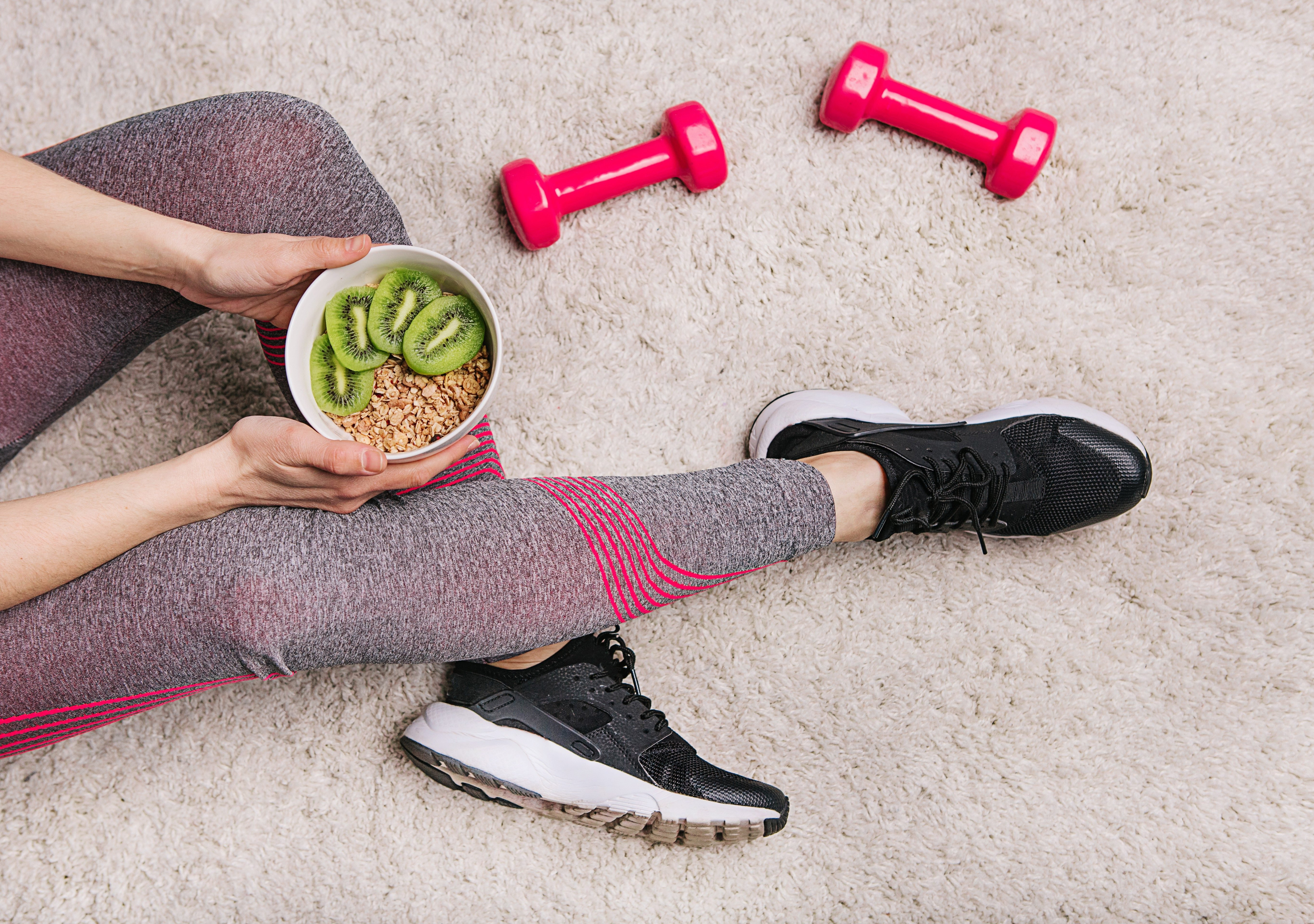 girl in sporting elk holds a plate with muesli and kiwi after fitness workout with dumbbells