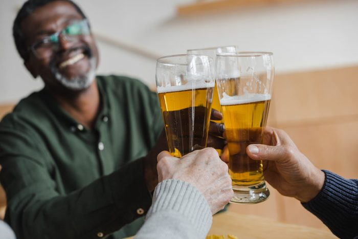 mature african american man clinking glasses of beer with friends
