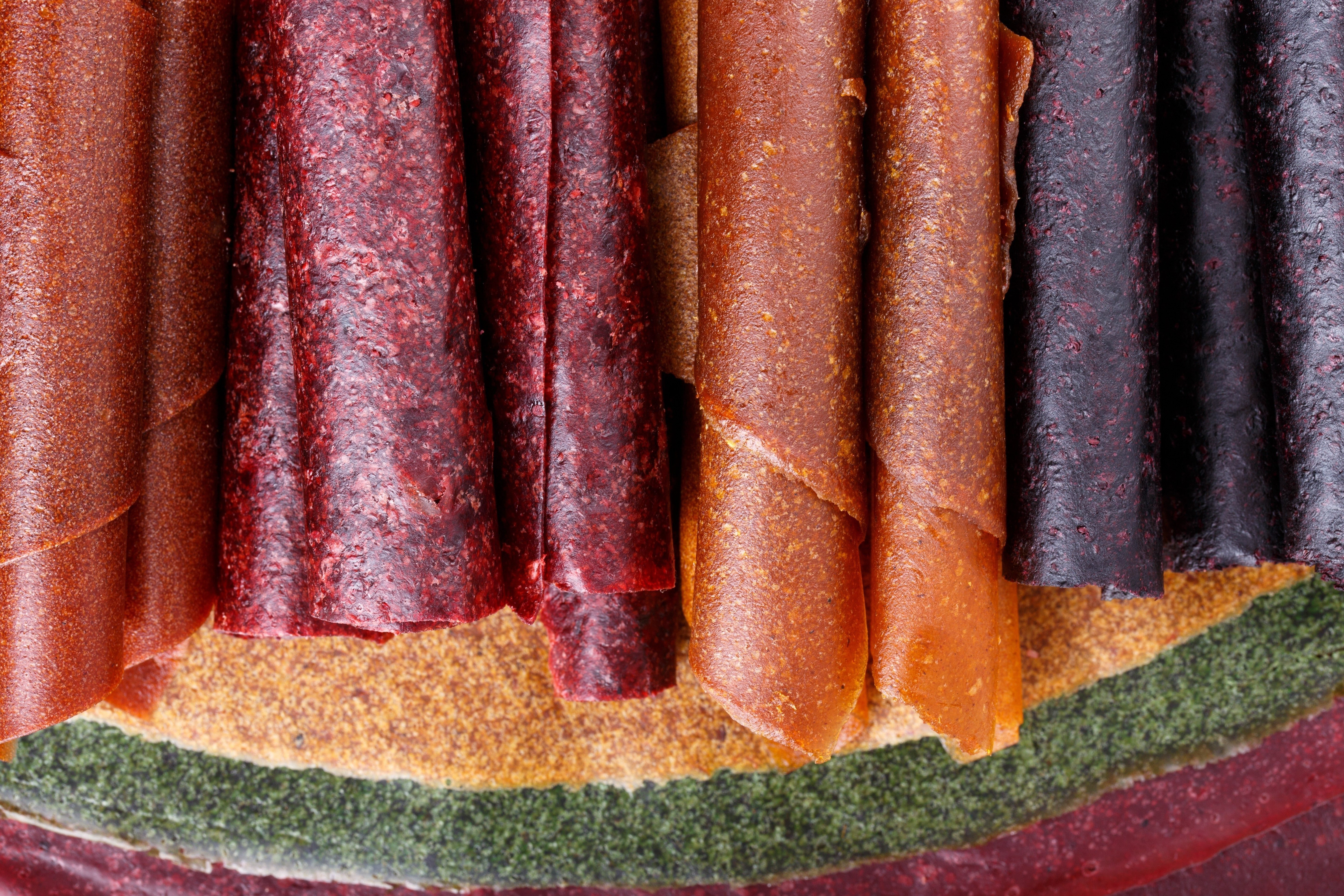 Colorful fruit leather rolls on mats of crushed fruit ( tklapi ). Fruit candy - pastille. Top view.