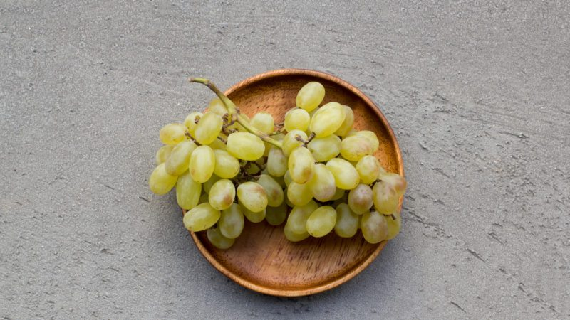 Fresh green seedless grapes on a wood platter isolated on grey background.