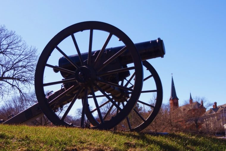 historic war cannon on a grass covered hill with church in background Stillwater Minnesota