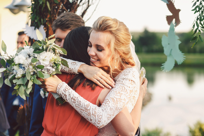 Bride in lace dress hugs woman in peeach gown tender