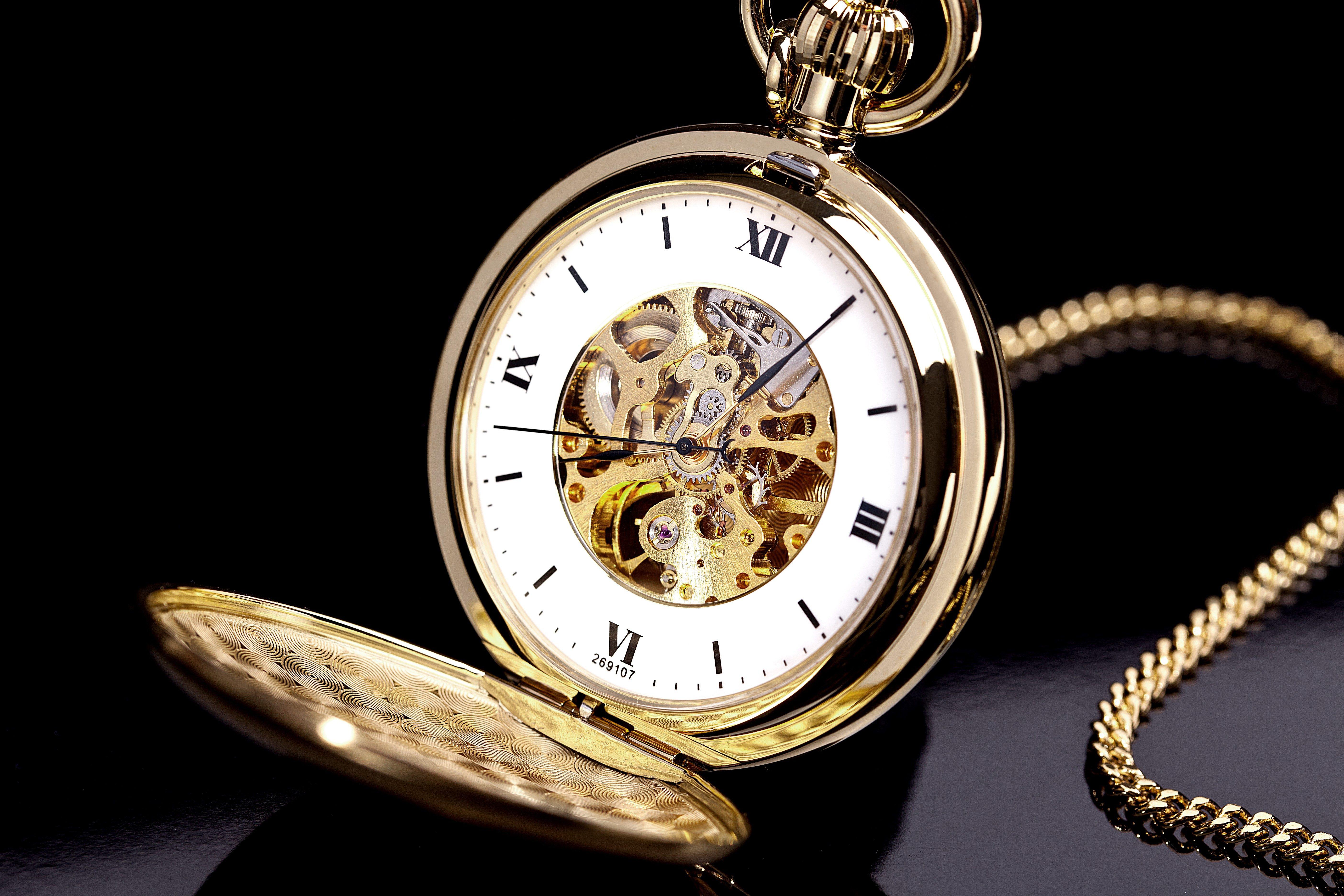 Gold pocket watch on a black background