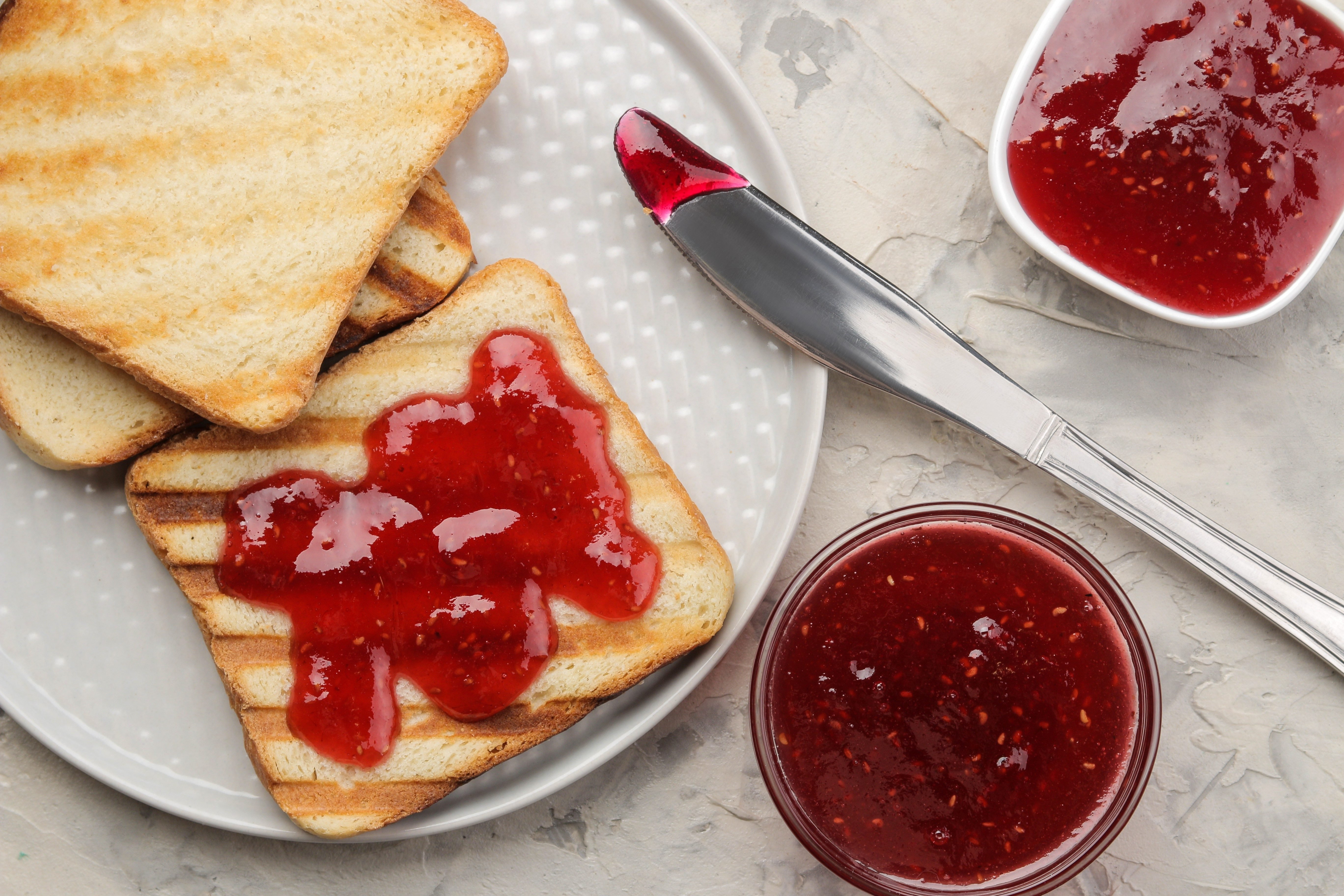 toasts with jam. fried crispy toasts with red jam on a light concrete table. breakfast. top view